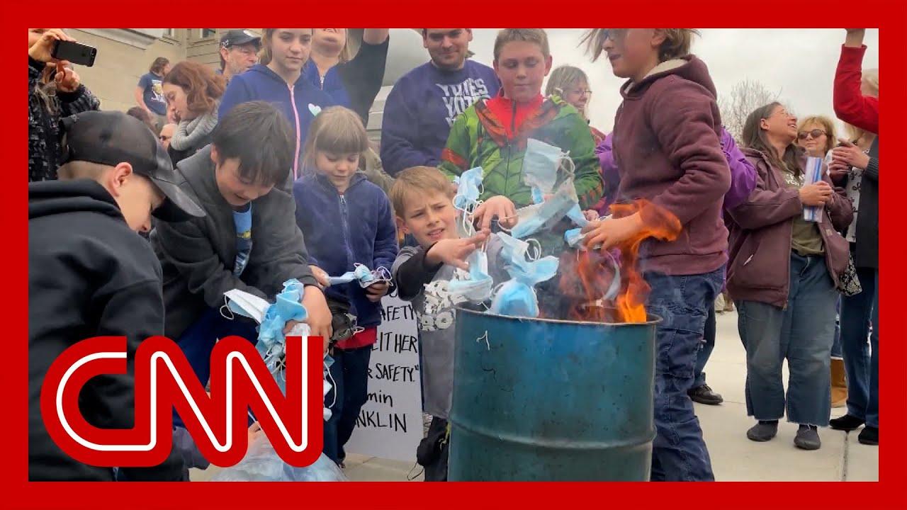 Children burn masks at rally